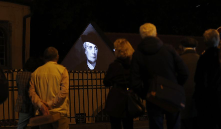 People watch as photographs of Czech Jews who were killed by the Nazis during World War II are projected on the outer wall of a Jewish bath at the Pinkas Synagogue in Prague, Czech Republic, Monday, Oct. 16, 2017. (AP Photo/Petr David Josek)