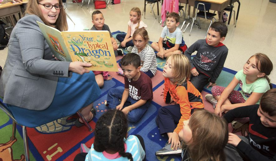 """In this photo taken Oct. 11, 2017, Jennifer Thompson, left, principal and coordinator of instruction of the Green Township School District, reads the book """"Not Your Typical Dragon"""" to first-grade teacher Lisa Sprofera's class at the Green Hills School in Green Township, N.J. Thompson, who is from Byram Township, N.J., began her tenure as the school district's principal in Sept. 2017, and is focusing on the philosophy """"Be better today than you were yesterday"""" to serve as the K-8 school's educational foundation for the years ahead. (Tracy Klimek/New Jersey Herald via AP)"""