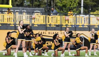 In this Saturday, Sept. 30, 2017 photo, five Kennesaw State University cheerleaders take a knee during the national anthem prior to a college football game against North Greenville, in Kennesaw, Ga. The group of cheerleaders from the college in Georgia say they'll take a knee in the stadium tunnel when the national anthem is played at Saturday's homecoming game since their university moved them off the field after an earlier demonstration. (Cory Hancock/Atlanta Journal-Constitution via AP)