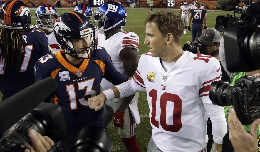 Denver Broncos quarterback Trevor Siemian (13) greets New York Giants quarterback Eli Manning (10) after an NFL football game Sunday, Oct. 15, 2017, in Denver. The Giants won, 23-10. (AP Photo/Joe Mahoney)