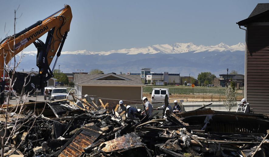 FILE - In this May 4, 2017, file photo, workers dismantle the charred remains of a house where an explosion killed two people in Firestone, Colo. Investigators blamed the explosion on gas leaking from a flow line that was believed to be out of service but was still connected to a well. Colorado is proposing tighter rules for taking oil and gas pipelines out of service after the incident. (AP Photo/Brennan Linsley, File)