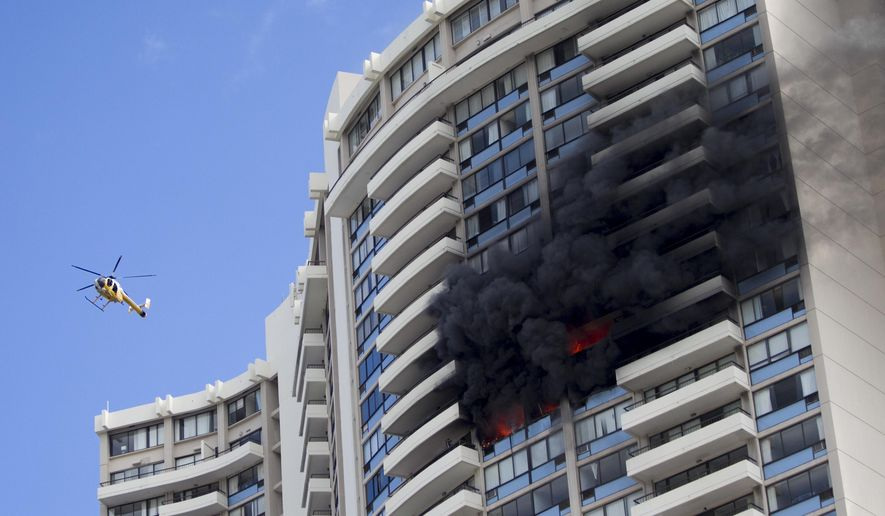 FILE--In this July 14, 2017, file photo, a Honolulu Fire Department helicopter flies near a fire burning on a floor at the Marco Polo apartment complex in Honolulu. Officials in Honolulu plan to release the investigation into the deadly fire that killed three residents of the 36-story apartment building. (AP Photo/Marco Garcia, file)