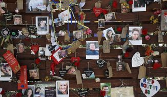 Photos and notes adorn a wall at the Las Vegas Community Healing Garden, Monday, Oct. 16, 2017, in Las Vegas. The garden was built as a memorial for the victims of the recent mass shooting in Las Vegas. (AP Photo/John Locher)