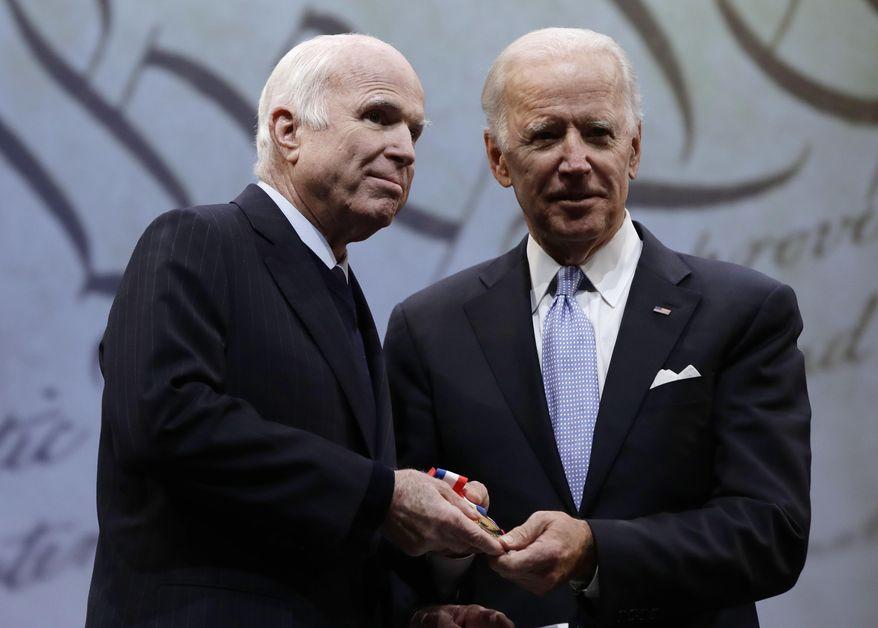 Sen. John McCain, R-Ariz., receives the Liberty Medal from Chair of the National Constitution Center's Board of Trustees, former Vice President Joe Biden in Philadelphia, Monday, Oct. 16, 2017. (AP Photo/Matt Rourke)