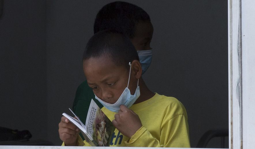 In this photo taken Tuesday Oct. 10, 2017, a girl wears a face mask inside a hospital in the capital Antananarivo, Madagascar.  A plague outbreak has brought some panic to the city dwellers with schools closed and public gatherings banned as the death toll still mounts in the Indian Ocean island nation.  (AP Photo/Alexander Joe)