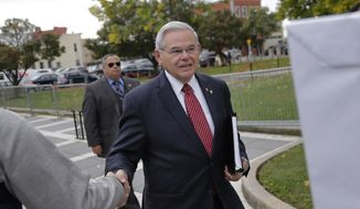 """U.S. Senator Robert Menendez greets supporters as he arrives to court in Newark, N.J., Monday, Oct. 16, 2017. The judge in Menendez's corruption trial could rule on Monday to dismiss the bulk of the indictment against the New Jersey Democrat, a decision that prosecutors say could """"broadly legalize pay-to-play politics."""" (AP Photo/Seth Wenig)"""