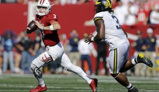 Indiana quarterback Peyton Ramsey, left, runs from Michigan defensive lineman Rashan Gary during the second half of an NCAA college football game in Bloomington, Ind., Saturday, Oct. 14, 2017. Michigan won 27-20 in overtime. (AP Photo/AJ Mast)