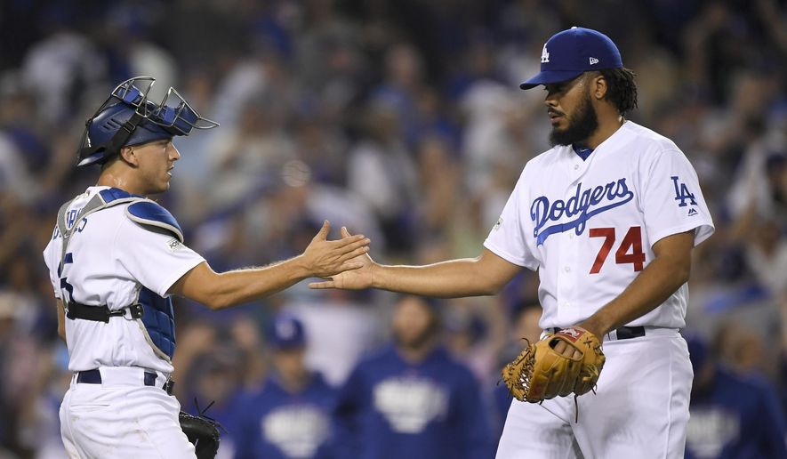 Los Angeles Dodgers relief pitcher Kenley Jansen, right, celebrates the team's 5-2 win with catcher Austin Barnes after Game 1 of baseball's National League Championship Series against the Chicago Cubs in Los Angeles, Saturday, Oct. 14, 2017.(AP Photo/Mark J. Terrill) **FILE**