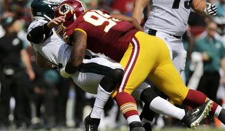 File-This Sept. 10, 2017, file photo shows Washington Redskins defensive end Jonathan Allen, right, tackling Philadelphia Eagles quarterback Carson Wentz as Wentz throws a pass in the first half of an NFL football game in Landover, Md. Allen, a rookie, has a Lisfranc sprain in his foot and will miss some time, according to coach Jay Gruden.(AP Photo/Mark Tenally, File)