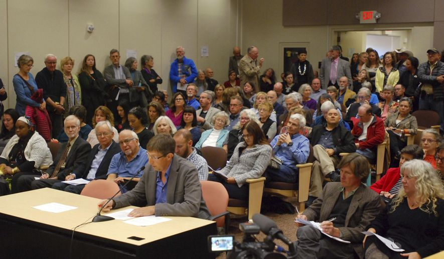 William Pockman (seated at table), a professor and chairman of the biology department at the University of New Mexico, speaks at a public hearing Monday, Oct. 16, 2017, in Santa Fe, N.M. Pockman said proposed state revisions to science standards for public schools would put local students at a disadvantage in the study of genetics in medicine and solutions to climate change. (AP Photo/Morgan Lee)