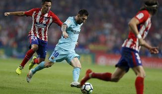 Barcelona's Lionel Messi , centre, sidesteps Atletico Madrid's Nicolas Gaitan during a Spanish La Liga soccer match between Atletico Madrid and Barcelona at the Metropolitano stadium in Madrid, Saturday, Oct. 14, 2017. The match ended in a 1-1 draw. (AP Photo/Francisco Seco)
