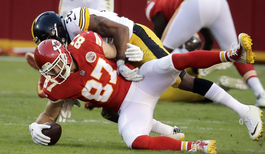 Kansas City Chiefs tight end Travis Kelce (87) recovers the ball he fumbled during a tackle by Pittsburgh Steelers linebacker Ryan Shazier (50) during the second half of an NFL football game in Kansas City, Mo., Sunday, Oct. 15, 2017. (AP Photo/Charlie Riedel)
