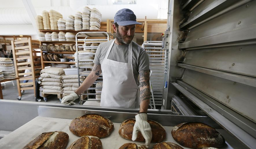 In this photo taken Friday, Aug. 11, 2017, Chad Robertson looks over loaves of bread coming out of an oven at the Tartine Manufactory in San Francisco. For a bread lover, no destination is more alluring than San Francisco. (AP Photo/Eric Risberg)