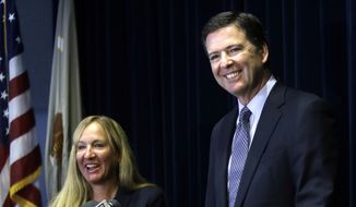 In this Oct. 1, 2014, file photo, then-FBI Director James B. Comey, right, is joined by U.S. Attorney Amanda Marshall during a news conference in Portland, Ore. (AP Photo/Don Ryan, File)