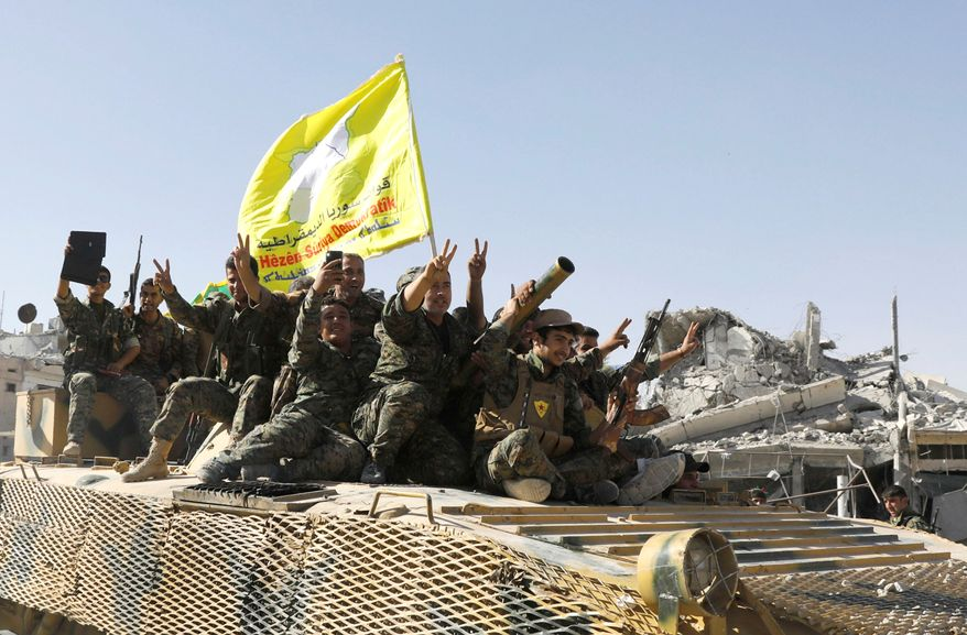 Syrian Democratic Forces fighters ride atop of military vehicle as they celebrate victory in Raqqa, Syria. (Reuters)