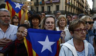 A woman holds an''estelada'' or Catalonia independence flag as people protest the National Court's decision to imprison civil society leaders without bail,  in front of the Palau Generalitat in Barcelona, Spain, Tuesday, Oct. 17, 2017.  Protesters were gathering for a fresh round of demonstrations in Barcelona Tuesday to demand the release of two leaders of Catalonia's pro-independence movement who were jailed in a sedition probe. (AP Photo/Manu Fernandez)