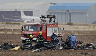 Emergency services work at the scene of a plane crash in Torrejon, just outside of Madrid, Spain, Tuesday, Oct. 17, 2017. An F-18 fighter jet crashed Tuesday at an air base outside Madrid, killing its pilot, the Spanish Defense Ministry said. A ministry spokesman said the F-18 jet crashed at the Torrejon de Ardoz base during takeoff. No one else was on the plane at the time.(AP Photo/Paul White)