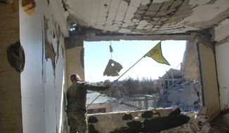In this picture taken on Monday Oct. 16, 2017, and provided by The Syrian Democratic Forces (SDF), a U.S.-backed Syrian Kurdish forces outlet that is consistent with independent AP reporting, shows a Syrian Democratic Forces (SDF) fighter, waves his Kurdish party flag at the front line where they battle against the Islamic State militants, in Raqqa, Syria. The U.S-backed Syrian forces battling the Islamic State group in Syria say Raqqa's national hospital, one of the militants' last holdouts in city has been captured. (Syrian Democratic Forces via AP)