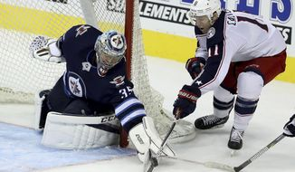 Winnipeg Jets' goaltender Steve Mason (35) stops Columbus Blue Jackets' Matt Calvert (11) during the third period of an NHL hockey game in Winnipeg, Manitoba, Tuesday, Oct. 17, 2017. The Blue Jackets won, 5-2. (Trevor Hagan/The Canadian Press via AP)