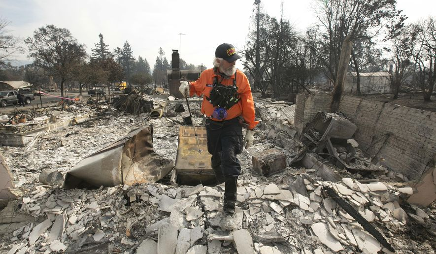 J. Petrocelli of the Alameda County Sheriff's Office Search and Rescue walks through the burned out remains of a home while searching the Coffey Park area Tuesday, Oct. 17, 2017, in Santa Rosa, Calif. A massive wildfire swept through the area last week destroying thousands of housing and business and taking the lives of more than two dozen people.(AP Photo/Rich Pedroncelli)