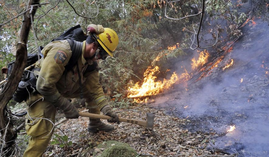 A firefighter builds a containment line as he battles a wildfire Tuesday, Oct. 17, 2017, near Boulder Creek, Calif. (AP Photo/Marcio Jose Sanchez)