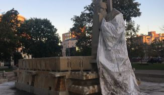 The Fountain of the Pioneers in Bronson Park was covered with a tarp on Monday, Oct. 16, 2017 in Kalamazoo, Mich. Officials in Kalamazoo have agreed to recognize Indigenous Peoples Day instead of Columbus Day, but the city hasn't decided what to do with a statue that some say celebrates the forced removal of Native Americans. (Malachi Barrett/ MLive.com via AP)
