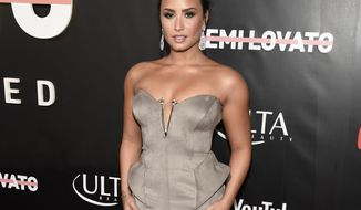 "FILE - In this Oct. 11, 2017 file photo, Demi Lovato arrives at the premiere of her documentary, ""Demi Lovato: Simply Complicated"" in Los Angeles. In the film, Lovato spills the beans about her years of drug abuse, her eating disorder and even the time she angrily punched one of her backup dancers in the face. (Photo by Chris Pizzello/Invision/AP, File)"