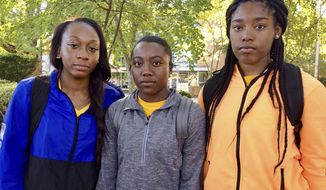 Kennesaw State University cheerleaders, from left to right,  Shlondra Young, Tommia Dean and Kennedy Town stand outside the student center on the school's campus in Kennesaw, Ga., Monday, Oct. 16, 2017. The three are part of a group of cheerleaders from the Georgia college that say they'll take a knee in the stadium tunnel when the national anthem is played at Saturday's homecoming game since their university moved them off the field after an earlier demonstration. (AP Photo/Jeff Martin)