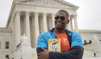 """In this Oct. 13, 2017, photo, Bryant Johnson, personal trainer for Supreme Court Justice Ruth Bader Ginsburg poses in Washington, with his new book, """"The RBG Workout: How She Stays Strong ... and You Can Too!"""" Besides the 84-year-old Ginsberg, Johnson, who now also trains Justice Stephen Breyer and Justice Elena Kagan. Johnson says he hopes the book will help convince people: """"You're never too old to do something.""""  (AP Photo/J. Scott Applewhite)"""