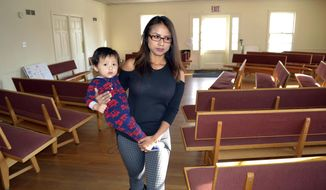 FILE - In this Dec. 8, 2016 file photo, Ingrid Encalada Latorre walks with her son Anibal while taking sanctuary at a Denver Quaker center, the Mountain View Friends Meeting, in Denver. She left the center in May 2017 but has taken sanctuary in another church to avoid deportation to her native Peru after Colorado Gov. John Hickenlooper refused to grant her a pardon. She was convicted in 2010 of possessing falsified or stolen identification papers. (AP Photo/P. Solomon Banda, File)
