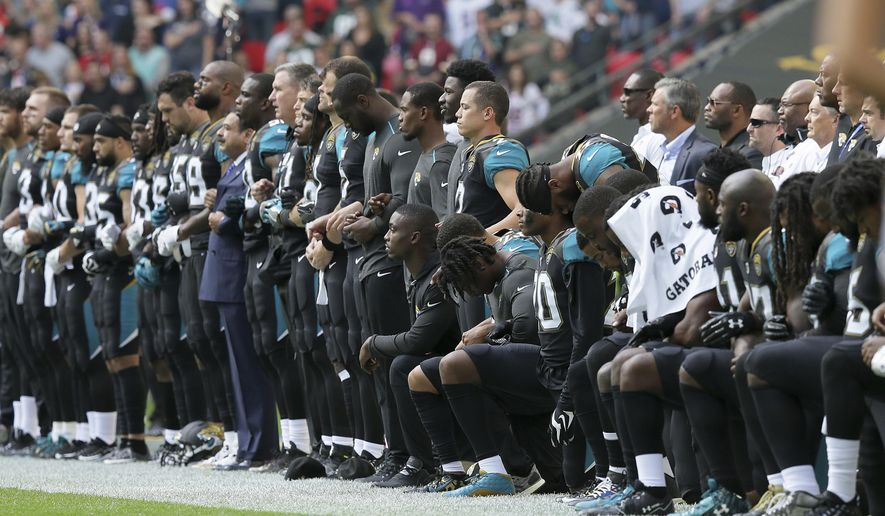 "FILE - In this Sept. 24, 2017, file photo, Jacksonville Jaguars NFL football players are shown, some standing an some kneeling, during the playing of the national anthem before an NFL football game against the Baltimore Ravens at Wembley Stadium in London. On Nov. 11, the NFL announced it had made ""no change"" to its national anthem policy as the league heads into Veterans Day weekend. (AP Photo/Tim Ireland, File)"