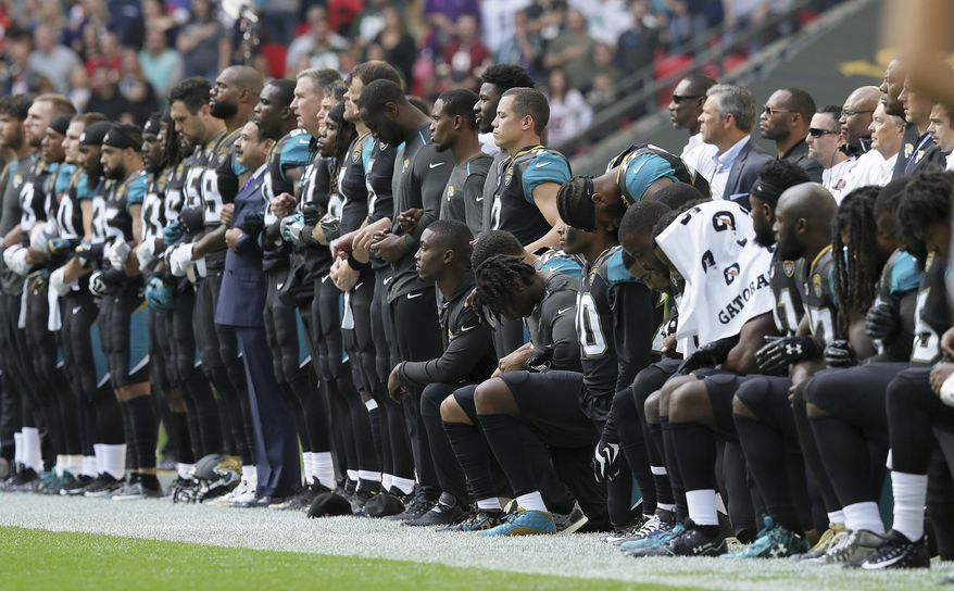 """FILE - In this Sept. 24, 2017, file photo, Jacksonville Jaguars NFL football players are shown, some standing an some kneeling, during the playing of the national anthem before an NFL football game against the Baltimore Ravens at Wembley Stadium in London. On Nov. 11, the NFL announced it had made """"no change"""" to its national anthem policy as the league heads into Veterans Day weekend. (AP Photo/Tim Ireland, File)"""