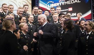 Sen. John McCain, R-Ariz., meets with members of the United States Naval Academy Choir after he received the Liberty Medal at the National Constitution Center in Philadelphia, Monday, Oct. 16, 2017. The honor is given annually to an individual who displays courage and conviction while striving to secure liberty for people worldwide. (AP Photo/Matt Rourke)