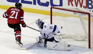 New Jersey Devils right wing Kyle Palmieri (21) scores a goal against Tampa Bay Lightning goalie Peter Budaj, of Slovakia, (31) during a shootout in an NHL hockey game, Tuesday, Oct. 17, 2017, in Newark, N.J. The Devils won 5-4 in a shootout. (AP Photo/Julio Cortez)