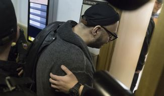 Russia's theater and film director Kirill Serebrennikov is escorted into a court room for hearings in Moscow, Russia, Tuesday, Oct. 17, 2017. Russia's Investigative Committee appealed for an extension of Serebrennikov's house arrest after he was  accused of scheming to embezzle around  $1.1 million in government funds allocated for one of his productions and the projects he championed between 2011 and 2014. (AP Photo/Pavel Golovkin)