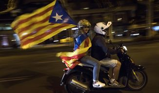 A woman holds an estelada or independence flag on a motorcycle after taking part on a protest against the National Court's decision to imprison civil society leaders without bail, in Barcelona, Spain, Tuesday, Oct. 17, 2017. Protesters were gathering for a fresh round of demonstrations in Barcelona Tuesday to demand the release of two leaders of Catalonia's pro-independence movement who were jailed in a sedition probe. (AP Photo/Emilio Morenatti)
