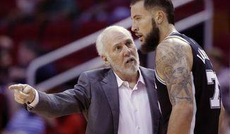 San Antonio Spurs head coach Gregg Popovich talks with San Antonio Spurs forward Joffrey Lauvergne (77) in the second half of an NBA preseason basketball game against the Houston Rockets Friday, Oct. 13, 2017, in Houston. (AP Photo/Michael Wyke)