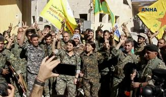 This frame grab from video released Tuesday, Oct. 17, 2017 and provided by Hawar News Agency, a Syrian Kurdish activist-run media group, shows fighters from the U.S.-backed Syrian Democratic Forces (SDF) celebrating their victory in Raqqa, Syria. U.S.-backed Syrian forces liberated the city of Raqqa from Islamic State militants on Tuesday, a senior commander for the force said, adding that clearing operations were underway to remove land mines left behind and search for the extremist group's sleeper cells. (Hawar News Agency via AP)