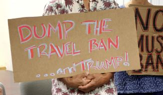 In this June 30, 2017, file photo, critics of President Donald Trump's travel ban hold signs during a news conference in Honolulu. On Tuesday, Oct. 17, 2017, a federal judge in Hawaii blocked the Trump administration from enforcing its latest travel ban, just hours before it was set to take effect. U.S. District Judge Derrick Watson granted Hawaii's request to temporarily block the policy from taking effect Wednesday. (AP Photo/Caleb Jones, File)