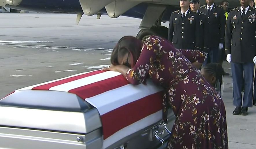 """ADDS TRUMP'S RESPONSE TO REP. WILSON - In this Tuesday, Oct. 17, 2017, frame from video, Myeshia Johnson cries over the casket of her husband, Sgt. La David Johnson, who was killed in an ambush in Niger, upon his body's arrival in Miami. President Donald Trump told the widow that her husband """"knew what he signed up for,"""" according to Rep. Frederica Wilson, who said she heard part of the conversation on speakerphone. In a Wednesday morning tweet, Trump said Wilson's description of the call was """"fabricated."""" (WPLG via AP)"""
