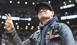 In this May 5, 2017, file photo, lead singer of The Tragically Hip Gord Downie salutes fans during the first half of Game 3 of an NBA basketball second-round playoff series between the Toronto Raptors and the Cleveland Cavaliers in Toronto. The widely revered lead singer died Tuesday night, Oct. 17, 2017. He was 53. (Frank Gunn/The Canadian Press via AP File)