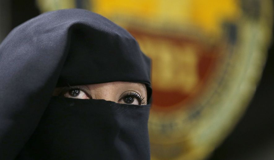 Wearing a burqa, Karen Aizha Hamidon, the widow of the leader of a militant band allegedly sympathetic to the Islamic State group, is presented to reporters during a news conference at the National Bureau of Investigation in Manila, Philippines, on Wednesday, Oct. 18, 2017. Authorities said she recruited foreign fighters to the country and spread extremist propaganda. (AP Photo/Aaron Favila)