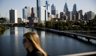 A woman crosses the South Street Bridge spanning the Schuylkill River and view of the Philadelphia skyline, Wednesday, Oct. 18, 2017. The cities of Philadelphia and Pittsburgh are both attempting to draw Amazon to build its second headquarters in Pennsylvania. (AP Photo/Matt Rourke)
