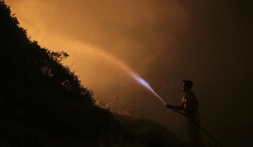 A volunteers uses a water hose to fight a wild fire raging near houses in the outskirts of Obidos, Portugal, in the early hours of Monday, Oct. 16 2017. Wildfires in Portugal killed at least 27 people, injured dozens more and left an unconfirmed number of missing in the country's second such tragedy in four months, officials said Monday. (AP Photo/Armando Franca)