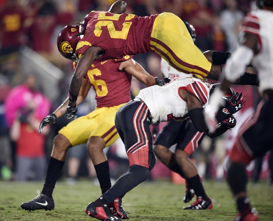 Southern California running back Ronald Jones II, top, jumps over Utah defensive back Marquise Blair to score a touchdown during the second half of an NCAA college football game in Los Angeles, Saturday, Oct. 14, 2017. USC won 28-27. (AP Photo/Kelvin Kuo)