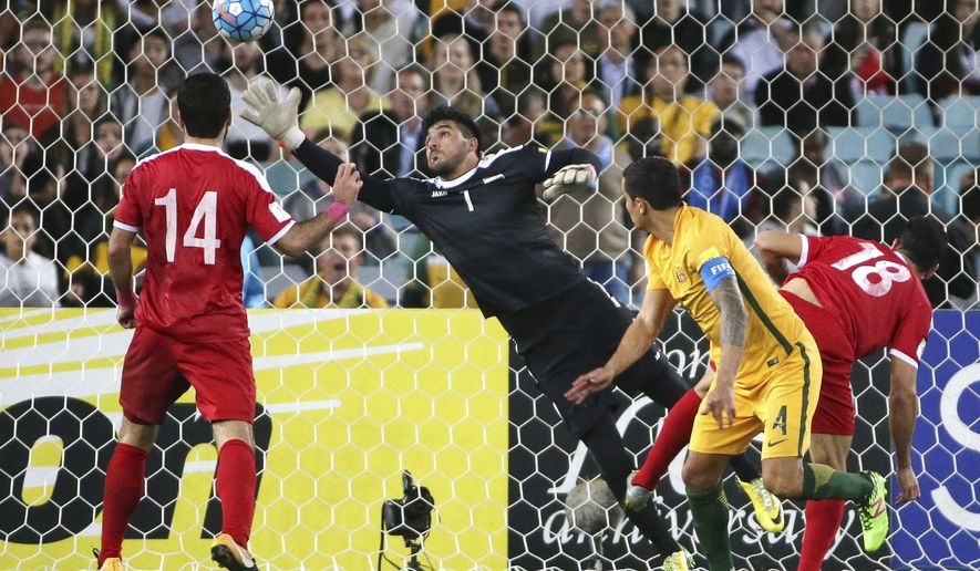 Syria's goal keeper Ibriham Alma, second left, is unable to stop the header from Australia's Tim Cahill, second right, from scoring during their Soccer World Cup qualifying match in Sydney, Australia, Tuesday, Oct. 10, 2017. (AP Photo/Rick Rycroft)