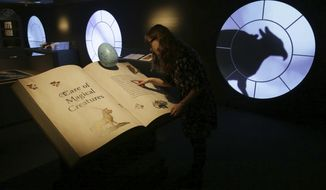 """A member of British Library staff poses for a picture at the """"Harry Potter - A History of Magic"""" exhibition at the British Library, in London, Wednesday Oct. 18, 2017.  The exhibition running from Oct. 20, marks the 20th anniversary of the publication of Harry Potter and the Philosopher's Stone, showing items from the British Library's collection, and items from author J.K Rowling and the book publisher's collection.  (AP Photo/Tim Ireland)"""