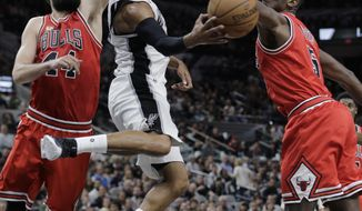 FILE - In this March 10, 2016, file photo, San Antonio Spurs guard Patty Mills, center, passes the ball as he is pressured by Chicago Bulls forward Nikola Mirotic (44) and forward Bobby Portis (5) during the second half of an NBA basketball game, in San Antonio.  The Bulls have suspended forward Bobby Portis for the first eight games for injuring teammate Nikola Mirotic during a fight at practice. Mirotic suffered multiple broken bones in his face as well as a concussion on Tuesday. He will likely need surgery and is out indefinitely. The team announced the suspension on Wednesday, Oct. 18, 2017. (AP Photo/Eric Gay, File)