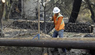 A Pacific Gas & Electric worker replaces power poles destroyed by wildfires on Wednesday, Oct. 18, 2017, in Glen Ellen, Calif. California fire officials have reported significant progress on containing wildfires that have ravaged parts of Northern California. (AP Photo/Ben Margot)