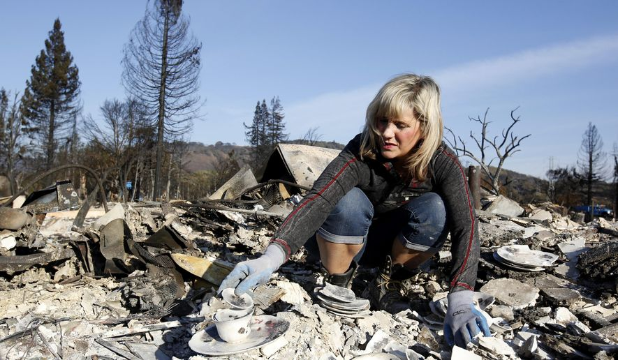 Debbie Wolfe stacks some china to take with her, that once belonged to her grandmother, found in the burned ruins of her home, Tuesday, Oct. 17, 2017, in Santa Rosa, Calif. A massive deadly wildfire swept through the area last week destroying thousands of housing and business. (AP Photo/Rich Pedroncelli)